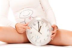Donna incinta con il grande orologio rotondo Immagini Stock Libere da Diritti