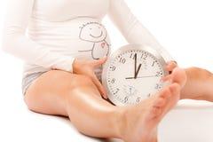 Donna incinta con il grande orologio rotondo Immagine Stock Libera da Diritti