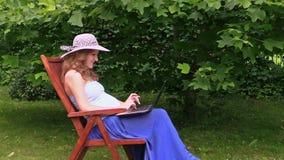 Donna incinta con il lavoro del cappello con il computer portatile che si siede sulla sedia di legno Fotografia Stock