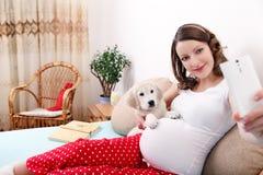 Donna incinta con il suo cane a casa Fotografie Stock