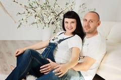 Donna incinta con il suo marito amoroso in un'anticipazione felice Immagine Stock