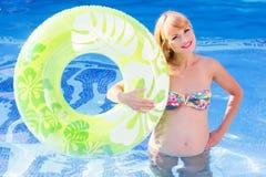 Donna incinta con l'anello di gomma verde nel nuoto fotografia stock