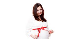 Donna incinta con l'arco rosso fotografia stock