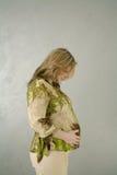 Donna incinta con la pancia verde della holding della camicetta Immagini Stock