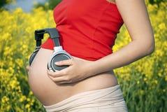 Donna incinta con le cuffie immagine stock