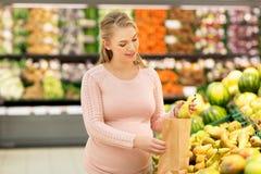Donna incinta con le pere d'acquisto della borsa alla drogheria Immagini Stock Libere da Diritti
