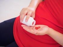 Donna incinta con le pillole della vitamina Immagini Stock