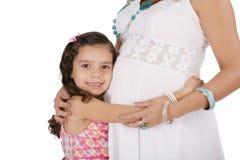 Donna incinta con sua figlia. Isolato sulle sedere bianche Immagine Stock
