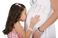 Donna incinta con sua figlia. Isolato sulle sedere bianche Fotografie Stock Libere da Diritti