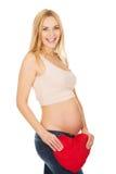 Donna incinta con un cuscino del cuore Fotografia Stock Libera da Diritti