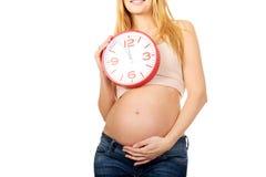 Donna incinta con un orologio Immagini Stock Libere da Diritti