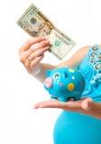 Donna incinta con una banca piggy Fotografie Stock Libere da Diritti
