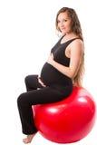 Donna incinta di forma fisica che fa esercizio su fitball su fondo bianco Immagine Stock