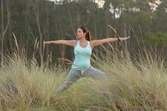 Donna incinta di forma fisica che fa esercizio di yoga all'aperto Fotografia Stock