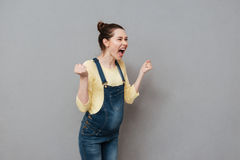 Donna incinta di grido che posa sopra la parete grigia immagine stock libera da diritti