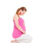 Donna incinta di smiley che si siede sul pavimento Fotografie Stock