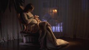 Donna incinta di Smilling con capelli lunghi che si siedono nella sedia di oscillazione nella stanza scura ed accarezzare la sua  archivi video