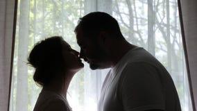 Donna incinta e un supporto dell'uomo contro una finestra in siluetta archivi video