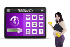 Donna incinta ed applicazioni di gravidanza Fotografia Stock