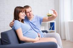 Donna incinta ed il suo marito che prendono la foto del selfie con pH astuto Fotografia Stock