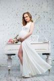 Donna incinta elegante in un vestito bianco classico vicino al piano bianco Fotografie Stock