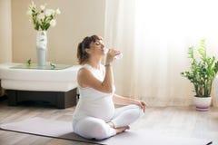 Donna incinta felice che beve acqua naturale dopo avere risolto immagini stock