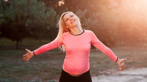 Donna incinta felice che gode del momento, tramonto Fotografia Stock