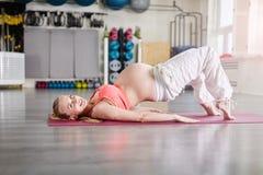 Donna incinta felice che prepara posa difficile di yoga Immagini Stock