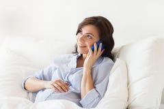 Donna incinta felice che rivolge allo smartphone a casa Fotografie Stock