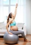 Donna incinta felice che si esercita sul fitball a casa Immagini Stock
