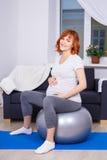 Donna incinta felice che si esercita sul fitball a casa Fotografia Stock