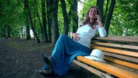 Donna incinta felice che si siede sul banco e sul telefono di conversazione Pancia femminile del colpo stock footage