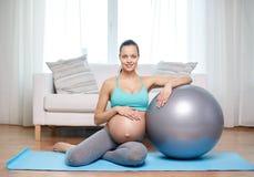 Donna incinta felice con fitball a casa Immagine Stock Libera da Diritti