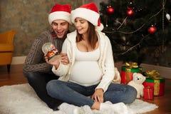 Donna incinta felice con i suoi cappelli d'uso di natale del marito fotografia stock libera da diritti