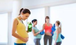Donna incinta felice con la bottiglia di acqua in palestra fotografie stock libere da diritti