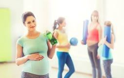 Donna incinta felice con la bottiglia di acqua in palestra Immagine Stock