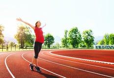 Donna incinta felice con le mani sollevate sullo stadio di sport Immagini Stock
