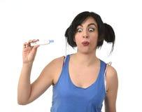 Donna incinta felice e sollevata controllando risultato negativo blu sul test di gravidanza Fotografia Stock