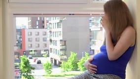 Donna incinta felice giovane che si siede sul davanzale a casa stock footage