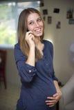 Donna incinta felice sul telefono Immagine Stock Libera da Diritti