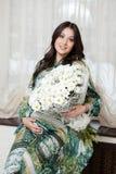 Donna incinta graziosa con i fiori delle camomille fotografia stock libera da diritti