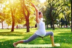 Donna incinta positiva che medita nella posa di yoga all'aperto Immagine Stock