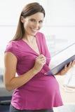 Donna incinta a scrittura del lavoro nel sorridere del raccoglitore Fotografia Stock Libera da Diritti
