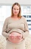 Donna incinta seria che rompe una sigaretta Fotografia Stock