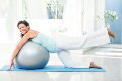 Donna incinta sorridente che allunga con la palla di esercizio Fotografia Stock