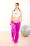 Donna incinta sorridente che fa le esercitazioni di forma fisica Fotografia Stock