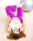 Donna incinta sorridente che fa le esercitazioni di forma fisica Immagine Stock