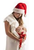 Donna incinta sorridente che porta il cappello di Santa isolato sopra bianco Immagine Stock