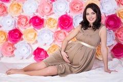 Donna incinta sorridente felice che si siede sopra il backg variopinto dei fiori Immagini Stock
