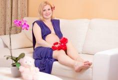 Donna incinta sorridente su un sofà Fotografia Stock Libera da Diritti